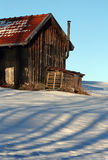 The old hut. An old hut in winter in bright and shade Royalty Free Stock Photo