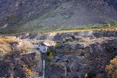 Old Hut Built On The Cliffs Of Shotover River Canyon. An historic building built into the rocky cliffs of Shotover Gorge in New Zealand Royalty Free Stock Images