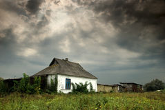 Old hut at the edge of a village. With dramatic sky Stock Photos