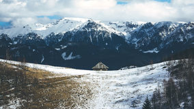 The old hut in the mountains. The old hut placed near the snowy Romanian Carpathians mountains Royalty Free Stock Photo