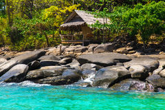 Old hut on stone beach of blue tropical sea Stock Images