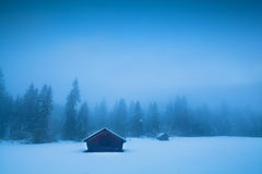 Old huts and coniferous forest in winter fog Royalty Free Stock Photography