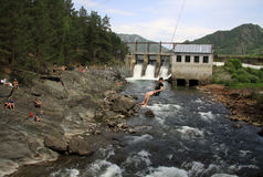 The old hydroelectric power station on the river Chemal in Altai mountains in Russia. Bungee jumping near power station. Stock Photos