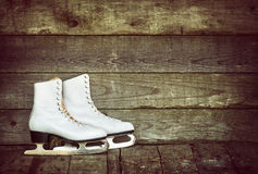 Old ice skates against rustic background Stock Photo