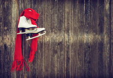 Old ice skates hanging on rustic wooden wall. Old ice skates with a red scarf hanging on rustic wooden wall. Vintage filter effects Stock Photos