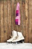 Old ice skates and scarf in the snow Royalty Free Stock Photos