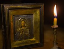 Old icon of Jesus Christ and a candle. Old icon of Jesus Christ and a burning candle Royalty Free Stock Photo