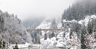 An old iconic Viaduct Bridge spans a snowy winter river stock images
