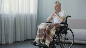 Old ill male sitting in wheelchair and praying, depression and terrible disease Royalty Free Stock Photos