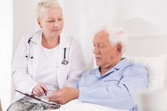 Old and ill patient. Has to sign papers Royalty Free Stock Photos