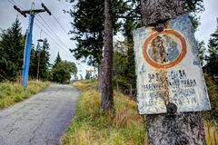 Old illegible sign. Old rusty unreadable metal sign by the cableway pole Stock Photos