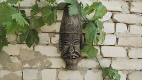 Old Inca or other empire mask hangs on brick concrete white wall. Scary face of ancient monster mask.