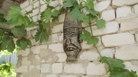 Old Inca or other empire mask hangs on brick concrete white wall. Scary face of ancient monster mask. Slow footage dolly