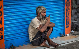Old Indian beggar sits in front of a closed shop and has a cup of morning tea on a road in South Kolkata, West Bengal, India. Stock Photo
