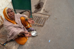 Old Indian beggar waits for alms on a street in Pushkar, India Royalty Free Stock Image