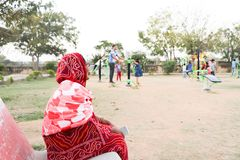 An old indian lady sitting on the bench and watching children playing in an open gym in a park stock photos