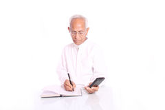 An old man calculating and writing Stock Photos