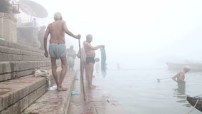 Old Indian men bathing in foggy Ganges river in Varanasi. VARANASI, INDIA - 19 FEBRUARY 2015: Old Indian men bathing in foggy Ganges river in Varanasi stock video footage