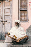 Old indian sadhu reading scriptures. Royalty Free Stock Photography