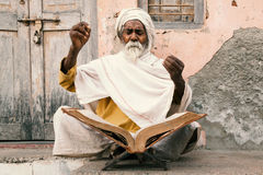 Old indian sadhu reading scriptures. Royalty Free Stock Image
