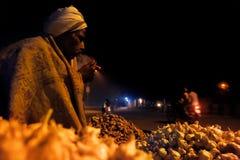 Old indian street vendor smoking in winter Royalty Free Stock Image
