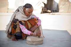 Old indian women on millstone grinding Royalty Free Stock Photography