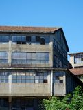 Old industrial building in abandonment. Old industrial building abandoned and in degradation invaded by climbing plants Royalty Free Stock Photo