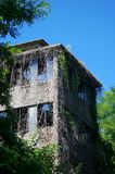 Old industrial building in abandonment. Old industrial building abandoned and in degradation invaded by climbing plants Stock Photos