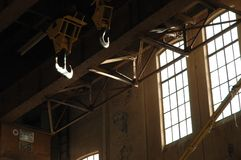 Old industrial factory hall. With crane hooks and sunlight falling through windows Stock Image