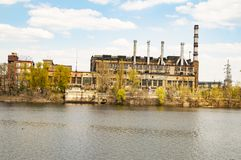 Old industrial factory with pipes on the river bank stock photos