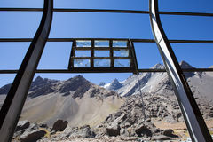 Old Industrial iron window frame and mountains, Argentina. Old Industrial iron window frame rusting with broken glass at abandoned train station at the border royalty free stock photos