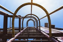 Old industrial ladder in to the sky. With sun Royalty Free Stock Image