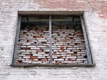 Old industrial loft building wall with big boarded up window. Old historical industrial loft building white colored big red bricks wall with big empty window Royalty Free Stock Image