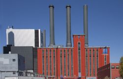 Old industrial power plant with new modern buildings against a blue sky, exterior view image. Stock photo royalty free stock photography