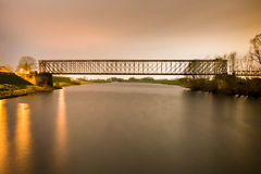 Old industrial railway railroad iron bridge center perspective o. Ver river in night Stock Photo