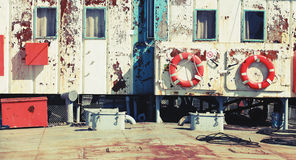 Old industrial ship rusted white superstructure. Wall with lifebuoys. Vintage retro stylized photo with tonal correction filter, instagram style Royalty Free Stock Photo