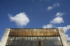 Old industrial warehouse. Detail of an old industrial unit against the cloudy sky Royalty Free Stock Image