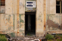 Old information sign above abandoned building entrance Royalty Free Stock Image