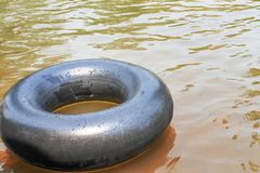 Old inner tubes with water drops and reflection from the sun floating on a river royalty free stock photography