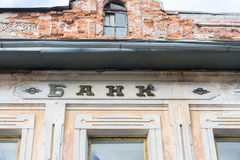 Old inscription Bank. Old crumbling brick Bank building with an old inscription BANK. The hard sign fell off stock images