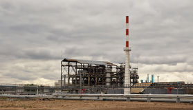 Old installation of a refinery smokestack under. Cloudy sky Stock Images