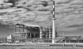 Old installation of a refinery smokestack under cloudy sky Royalty Free Stock Photo