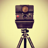 Old instant camera in a tripod. Picture of an old instant camera in a tripod with a retro effect Stock Photos