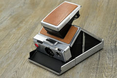 Old instant camera on wood floor. Being opened Royalty Free Stock Photos
