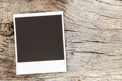 Old instant photo frame on wooden background. Old instant photo frame on the wooden background Stock Images