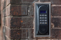 Old intercom on a red brick wall Stock Image