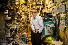 Old Iranian shoemaker showing one of his shoes for sell in his shop in the Isfahan covered bazar market. Picture of a senior shoemaker of Isfahan, Iran, showing stock photos