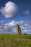 Old Irish castle ruin. S in green field with blue sky Stock Photo