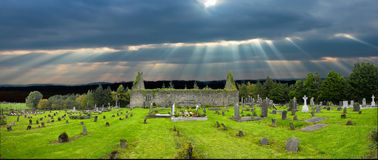 Old Irish church  grave yard. In the background an ancient Irish church is falling to time and in the foreground old grave stones and mixed with the new graves,a Royalty Free Stock Image