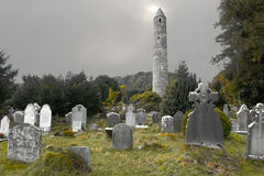 Old Irish church  grave yard. In the background an ancient Irish look out tower is falling to time and in the foreground old grave stones and mixed with the new Stock Photography
